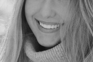 Frau mit langen Haaren zeigt ihre weißen Zähne