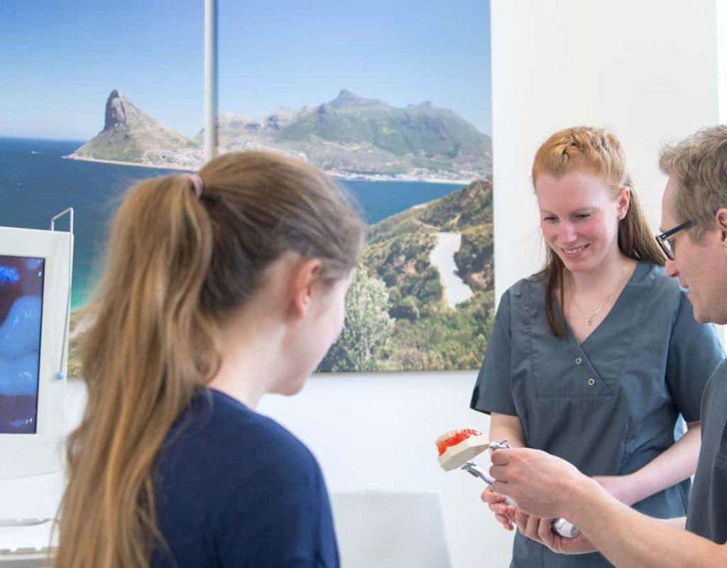 Zahnarzt Knsope im Gespräch mit Mitarbeiterin und Kundin